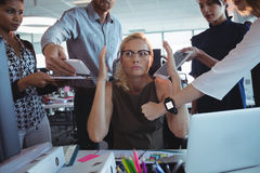 Irritated businesswoman sitting amidst team holding technologies. At office Royalty Free Stock Photography