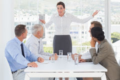 Irritated businesswoman talking to her colleagues Stock Photo