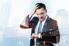 Irritated busy man having too little time. Hurry up. Busy hardworking manager being angry and irritated while looking at his smart watch and screaming Stock Images