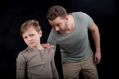 Irritated father holding shoulder of scared little son. Family problems concept Stock Image