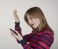 Irritated girl with smartphone Stock Image