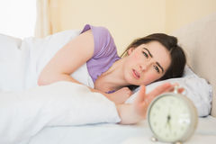 Irritated girl waking up in her bed Royalty Free Stock Image