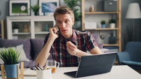 Irritated guy freelance worker is talking on mobile phone and using laptop expressing negative emotions working in stock footage