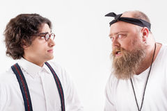 Irritated male hipster talking to frightened smart guy. Do you want to argue with me. Aggressive fat bearded men is bullying to scared slim outcast. Isolated Royalty Free Stock Photos