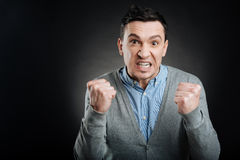 Irritated male person making fists. I am angry. Angry man, keeping his eyes wide opened while clenching his teeth standing  on black background Stock Photography
