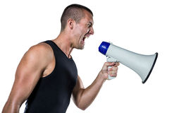 Irritated male trainer yelling through megaphone. Against white background Royalty Free Stock Images