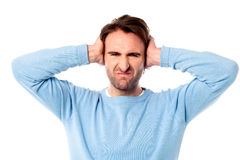 Irritated man blocking his ears Stock Photos