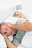 Irritated man blocking his ears from noise of wife snoring. Irritated men blocking his ears from noise of wife snoring at home in bedroom Royalty Free Stock Photography