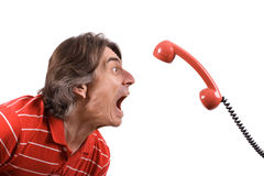 Irritated man screams into the telephone receiver. An angry and irritated man screams into the telephone receiver over a white background Stock Photography