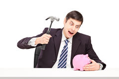Irritated man trying to break a piggy bank with a hammer. On white background Stock Photo