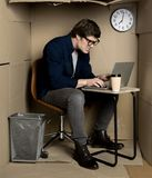 Irritated manager is laboring in confined carton room. Feeling furious. Full length of young employee is expressing anger while typing on modern laptop. He is stock photos