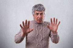 An irritated mature man with astonished and angry expression refusing something while showing no sign with his palms. Man wanting. To stop something showing no stock images