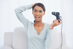 Irritated pretty woman sitting on sofa playing video games Stock Photography