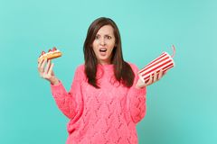 Irritated shocked young woman in knitted pink sweater hold in hands eclair cake, plastic cup of cola or soda isolated on. Irted shocked young woman in knitted stock photo