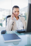 Irritated sophisticated businesswoman on the phone. In bright office royalty free stock photo