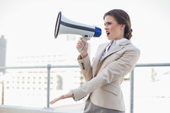 Irritated stylish brown haired businesswoman screaming in a megaphone Royalty Free Stock Images