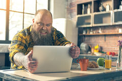 Irritated thick guy watching something on laptop. Do not tell me about healthy diet. Angry fat man is keeping his computer and looking at monitor with irritation Royalty Free Stock Photos