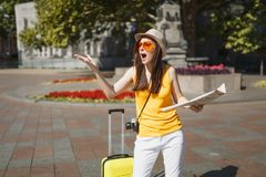 Irritated traveler tourist woman in orange heart glasses with suitcase holding city map spreading hands in city outdoor stock photos