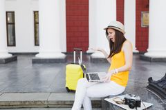 Irritated traveler tourist woman with suitcase sit on stairs using working on laptop pc computer spreading hands outdoor stock photos