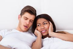 Irritated woman covering ears while man snoring in bed Royalty Free Stock Photos