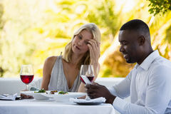 Irritated woman looking at man using phone at restaurant Stock Photos