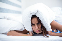 Irritated woman lying on bed Stock Photography