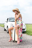 Irritated woman sitting on luggage by broken down car on country road Royalty Free Stock Images