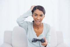Irritated woman sitting on sofa playing video games Royalty Free Stock Images