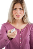 Irritated woman using remote control Royalty Free Stock Photography