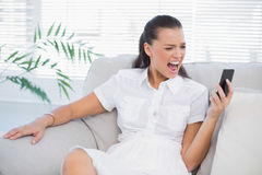 Irritated woman in white dress screaming at her smartphone. In bright living room Royalty Free Stock Photos