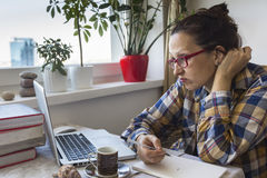 Irritated woman working on a laptop at home. Internet troll. Stock Photo