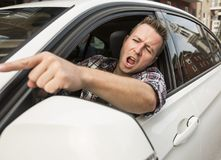 Irritated young man driving a car. Irritated driver Royalty Free Stock Photos