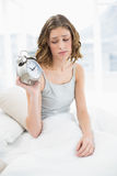Irritated young woman holding an alarm clock sitting on her bed Royalty Free Stock Image