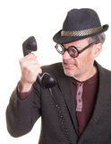 Irritating Phone Call. An angry nerdy old man receiving an unsolicited political or sales phone call on a vintage corded telephone Stock Photo
