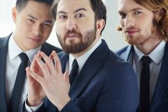 Irritation. Annoyed businessman looking at camera with his colleagues on background Royalty Free Stock Photo