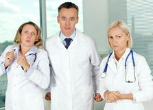 Irritation. Three clinicians in white coats looking at camera with annoyed expression Royalty Free Stock Images