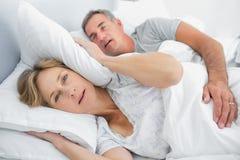 Irriterad fru som blockerar henne öron från oväsen av att snarka för make Arkivfoto