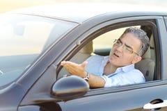 Irriterad manlig körande bil i trafik - vägursinnebegrepp Arkivfoto