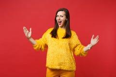 Irriterad ung kvinna i gul pälströja som skriker att göra en gest visa format med horisontalworkspace som isoleras på royaltyfri fotografi