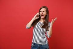 Irriterad ung kvinna som skriker fördelande händer som talar på mobiltelefonen som för konversation som isoleras på ljust rött royaltyfri foto