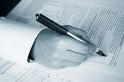 IRS Form. A woman filling the IRS form - monochrome Royalty Free Stock Image