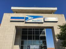 Close-up logo at facade entrance of USPS store in Irving, Texas,. IRVING, TX, USA-SEP 2, 2018:Close-up brand logo at exttorior of USPS store clear blue sky. The royalty free stock photo