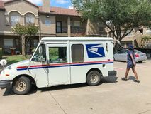 White USPS truck with woman carrier at apartment building complex in Texas, USA. IRVING, TX, USA-SEP 7, 2018:USPS vehicle with female postal carrier at apartment stock photography