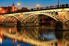 Triana bridge over Guadalquivir river in Seville. Isabel II bridge or Triana bridge over Guadalquivir river with it's reflection at twilight, Seville stock images