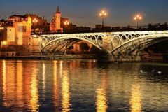 Isabel II bridge or Triana bridge over Guadalquivir river at twilight, Seville. Andalusia, Spain royalty free stock photography