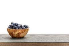 Isabella grapes in wood bowl on table, border Stock Image