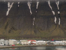 Isafjordur, Iceland. The fishing town of Isafjordur in Iceland with snow on the mountain on a cloudy day Stock Images