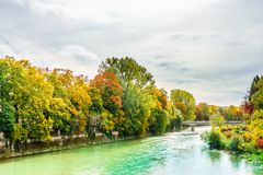 Isar river an colorful trees in autumn landscape in Munich. View on Isar river an colorful trees in autumn landscape in Munich Royalty Free Stock Image