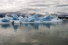 Isbergö med stora kvarter av is som svävar i vattnet arkivbild