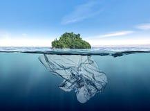 Isberg av avskrädeplast- med ön som svävar i havet royaltyfria bilder